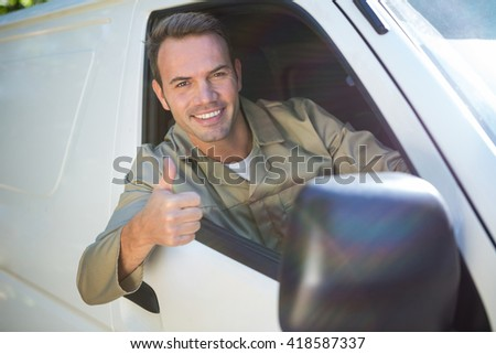 Portrait of delivery man sitting in his van with thumbs up - stock photo