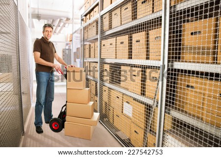 Portrait of delivery man with stacked cardboard boxes on hand truck at warehouse - stock photo