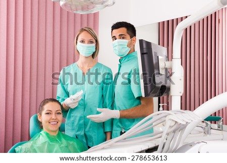 Portrait of dentist and adult european patient at dental clinic - stock photo
