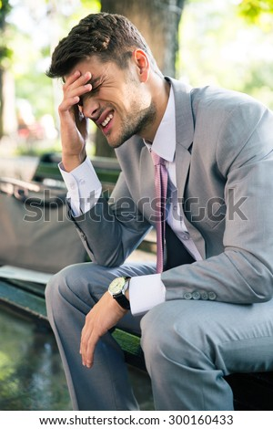 Portrait of depressed businessman sitting on the bench outdoors - stock photo