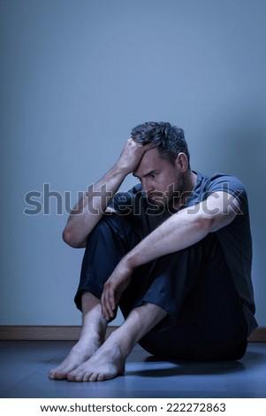Portrait of depressed man sitting on the floor - stock photo