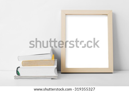 portrait of desk blank photo frame nest to stack of books with copy space on white background - stock photo