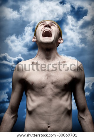 Portrait of despaired screaming man against dramatic sky - stock photo