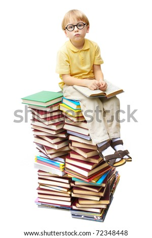 Portrait of diligent pupil sitting on top of books and looking at camera - stock photo