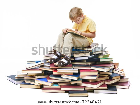 Portrait of diligent pupil sitting on top of books and reading - stock photo