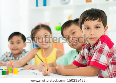 Portrait of diligent pupils sitting at the school desk - stock photo
