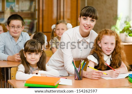 Portrait of diligent schoolgirl at lesson surrounded by her classmate and teacher - stock photo