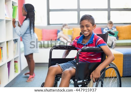 Portrait of disabled schoolboy on wheelchair in library at school - stock photo