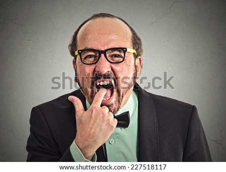 portrait of disgusted man with finger in mouth very displeased with situation service ready to vomit throw up isolated on grey wall background. Human face expression, emotion, feeling, body language - stock photo