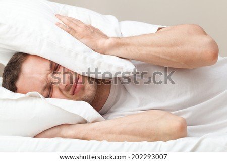 Portrait of dissatisfied Young Caucasian man in bed - stock photo