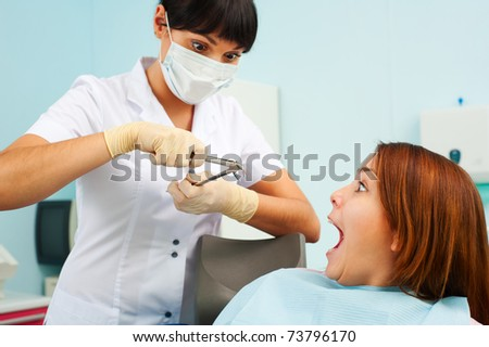 portrait of doctor and scared patient at dentist's office - stock photo