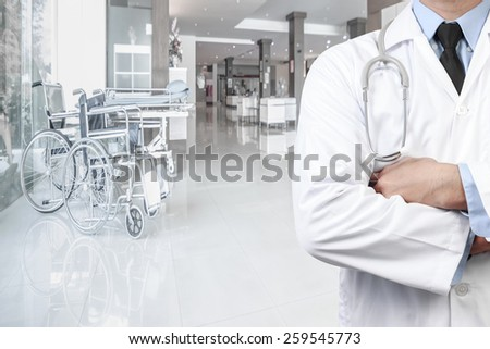 portrait of doctor and wheelchair on corridor of hospital - stock photo