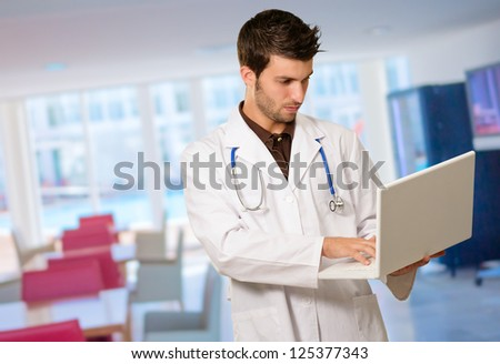 Portrait Of Doctor Holding Laptop, Indoors - stock photo