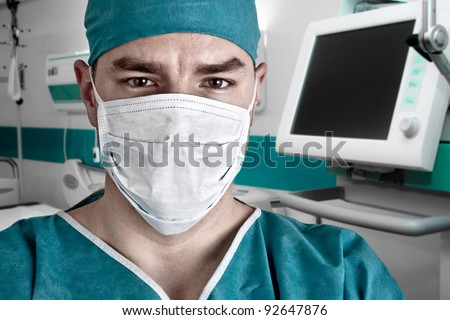 Portrait of doctor in scrubs and modern hospital room with computer and monitor - stock photo