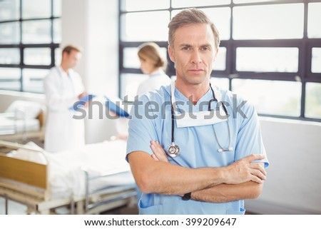 Portrait of doctor standing with arms crossed in hospital - stock photo