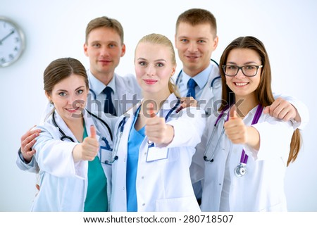 Portrait of doctors team showing thumbs up  - stock photo