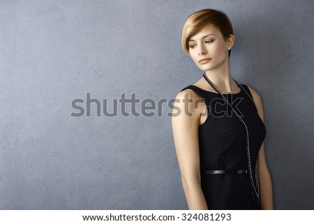 Portrait of dreamy young woman in black dress leaning to wall - stock photo