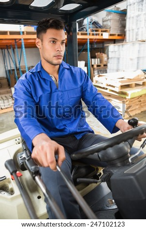Portrait of driver operating forklift machine in warehouse - stock photo