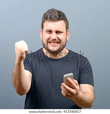 Portrait of ecstatic man holding cell phone and celebrating with closed fist against gray background - stock photo