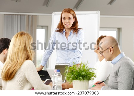 Portrait of efficiency business woman presenting project to business team while sitting at meeting.  - stock photo