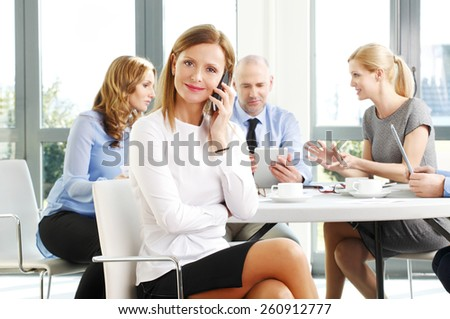 Portrait of efficiency sales woman making call while sitting at business meeting at office.  - stock photo