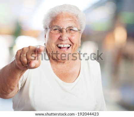 portrait of elder woman pointing to front with finger - stock photo