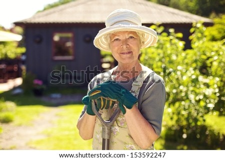 Portrait of elder woman with gardening tools outdoors. Senior woman standing with shovel in her backyard - stock photo