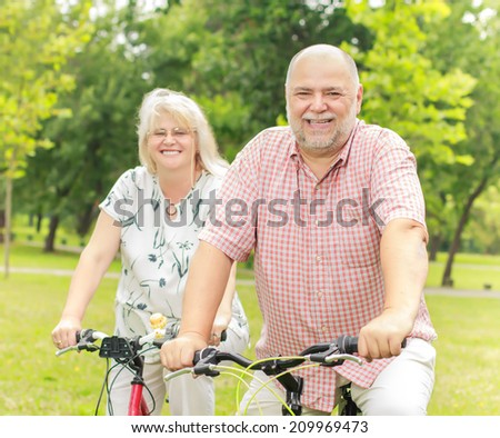 Portrait of elderly couple ride bike in the park. - stock photo