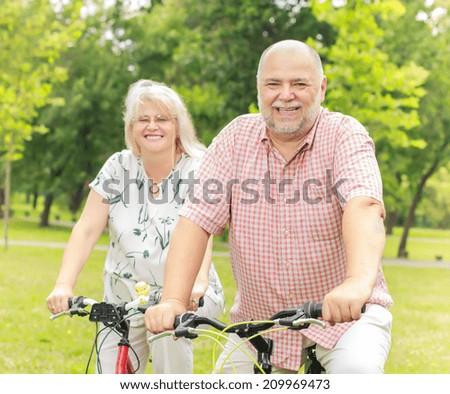Portrait of elderly couple ride bike in the park. - stock photo