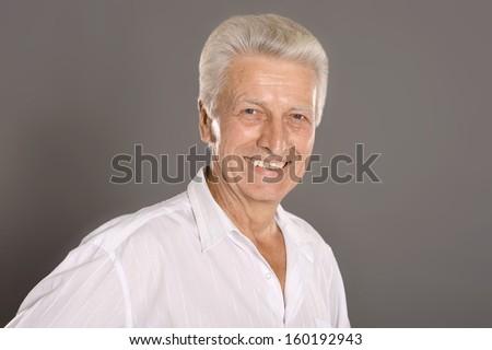 Portrait of elderly man isolated on grey background - stock photo