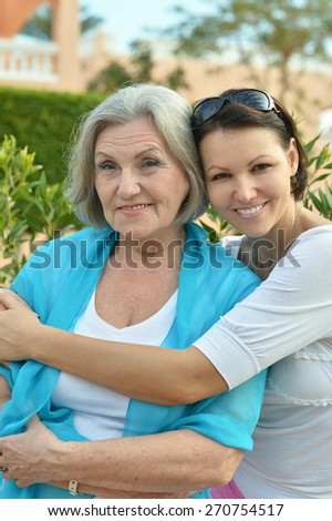 Portrait of elderly mother and daughter smiling happily - stock photo