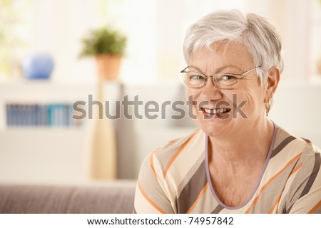 Portrait of elderly woman at home, looking at camera, smiling.? - stock photo