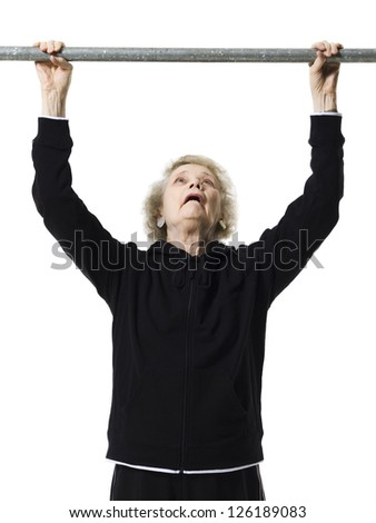 Portrait of elderly woman doing chin up exercises - stock photo