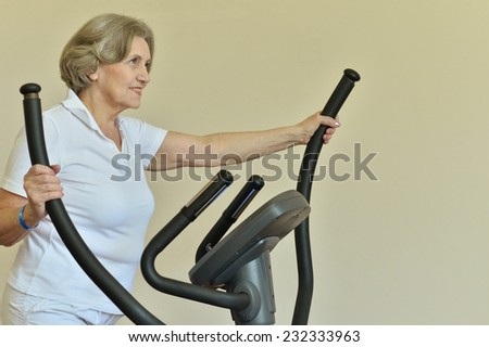 Portrait of elderly woman exercising in gym - stock photo