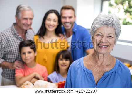 Portrait of elderly woman in the kitchen and other family member standing in background - stock photo
