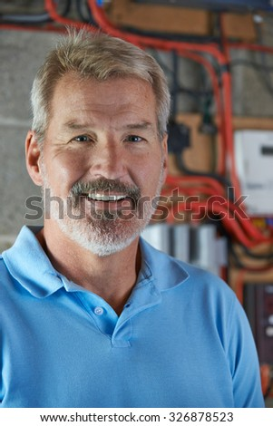 Portrait Of Electrician Standing Next To Fuseboard - stock photo