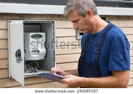 Portrait Of Electrician Worker Inspecting Electric Meter  - stock photo
