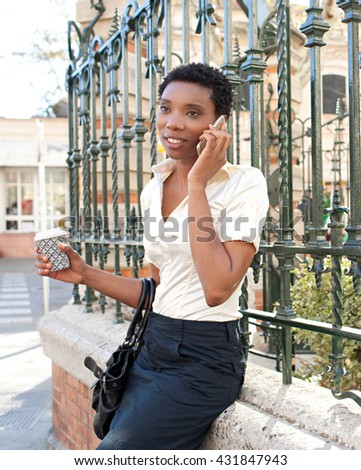 Portrait of elegant african american young business woman in classic city with wrought iron decorative fence, using smart phone on phone call, holding take away coffee mug, smiling in sunny outdoors. - stock photo