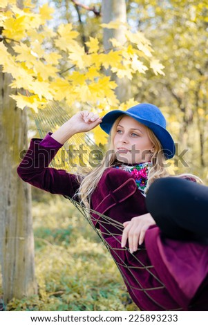 portrait of elegant beautiful blond young hipster woman having fun in hammock on sunny autumn day outdoors copy space background - stock photo