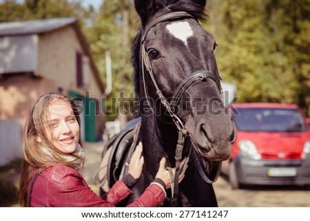 Portrait of elegant beautiful young woman embracing horse smiling outdoors - stock photo