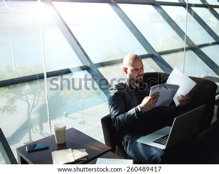 Portrait of elegant business man looking over some paperwork sitting next to big window in office interior, male executive studies documents or papers during his coffee time - stock photo