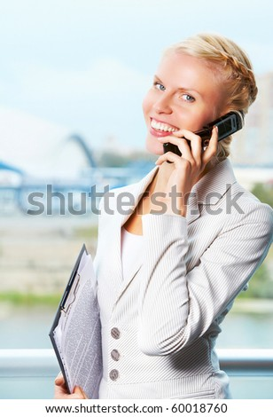 Portrait of elegant businesswoman looking at camera while speaking on the phone - stock photo