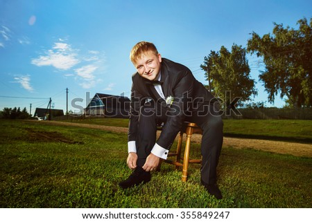 Portrait of elegant man in black suit putting on shoe at green summer grass lawn background. - stock photo