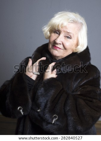 Portrait of elegant senior woman in fur coat  - stock photo