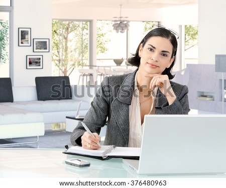 Portrait of elegant smart caucasian businesswoman at home desk, wearing suit, sitting in front of laptop computer, personal business organizer. Hand under chin, looking at camera, smiling. - stock photo