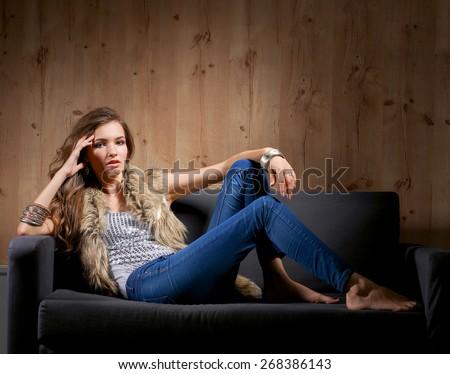 Portrait of elegant woman sitting on black sofa . - stock photo