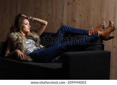 Portrait of elegant woman sitting on black sofa wearing a blue jeans and fur vest - stock photo