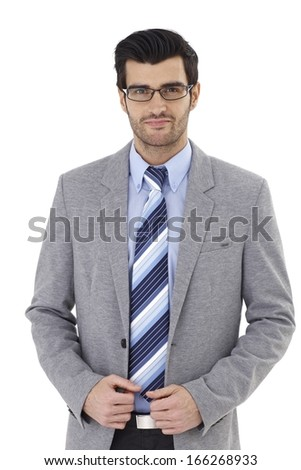 Portrait of elegant young businessman, looking at camera, smiling, wearing glasses. - stock photo