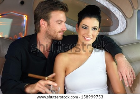 Portrait of elegant young couple sitting in limousine, smiling. - stock photo