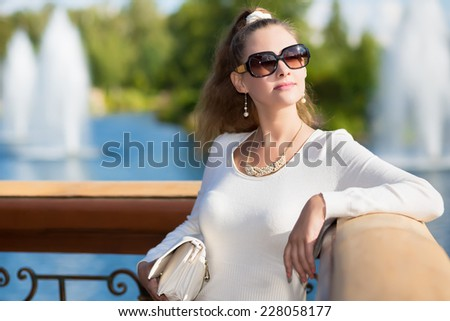 Portrait of elegant young woman in white dress and black sunglasses posing outside - stock photo